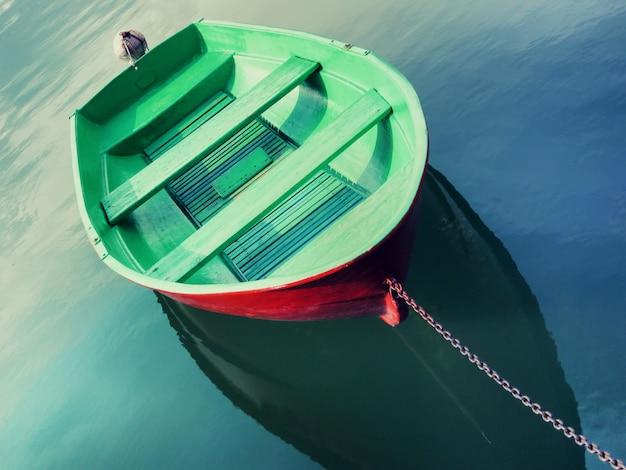 Único barco de pesca pintado em verde flutuando na água e amarrado com corrente metálica