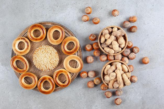 Único biscoito rodeado por sushki em uma placa de madeira ao lado de tigelas de amendoim e avelãs espalhadas no fundo de mármore. foto de alta qualidade