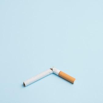 Único cigarro quebrado em sobre fundo azul