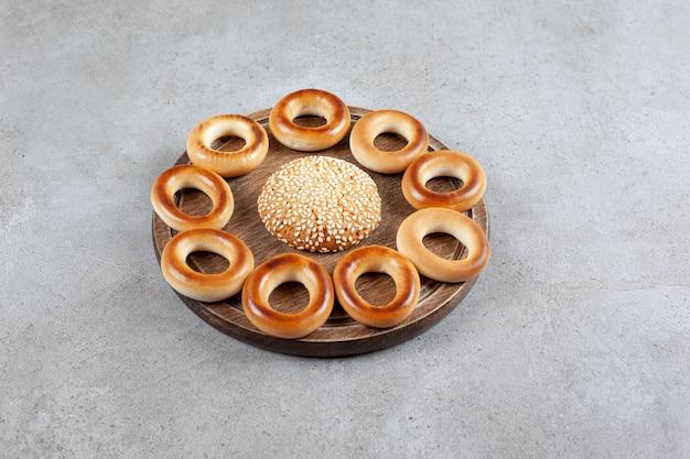 Único cookie rodeado por sushki em uma placa de madeira na superfície de mármore.