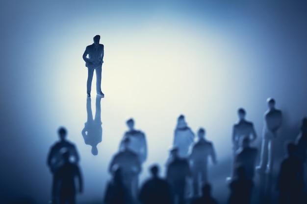 Único homem em pé na frente do grupo de pessoas.