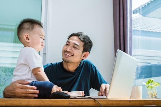 Único pai e filho usando laptop juntos alegremente