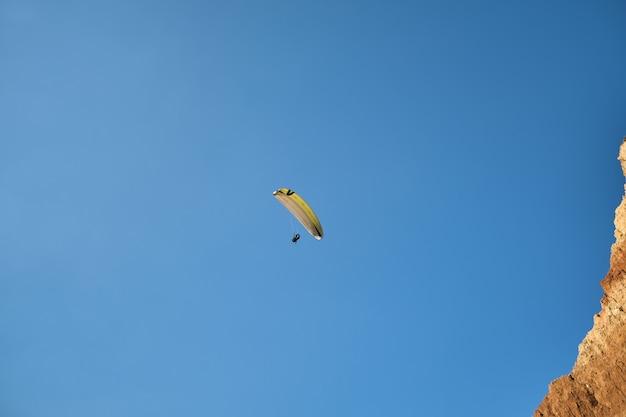Único parapente voando contra o céu azul. esportes radicais - parapente no céu tendo como pano de fundo uma bela paisagem com um penhasco arenoso