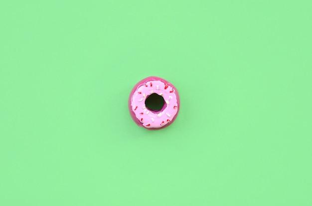 Único pequeno donut de plástico encontra-se em um fundo colorido pastel