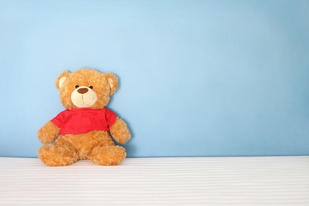 Único urso marrom boneca vestir camisa vermelha sentar na cama branca na parede de fundo azul no quarto