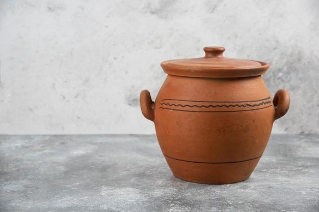 Único vaso antigo de barro colocado sobre uma superfície de mármore.