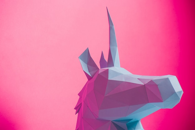 Unicórnio 3d de papel no lado esquerdo do fundo cor-de-rosa, horizontal. brinquedo de origami. origami pegasus