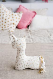 Unicórnio de brinquedo macio na cama com almofadas