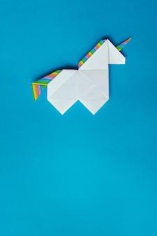 Unicórnio de origami branco sobre fundo azul