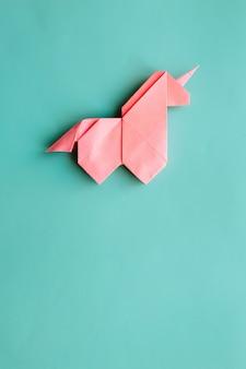 Unicórnio de origami rosa sobre fundo azul ciano