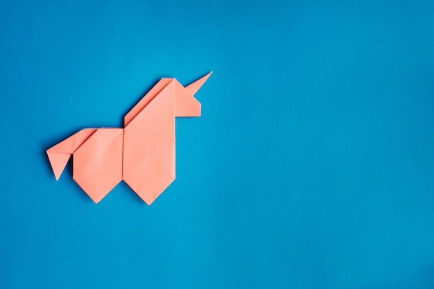 Unicórnio de origami rosa sobre fundo azul