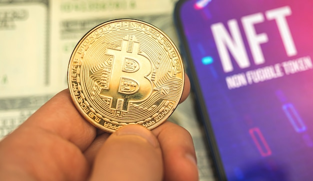 Unidade de criptografia de dados, bitcoin dourado em mãos e logotipo nft na tela, conceito de criptografia comercial e financeira e foto de fundo