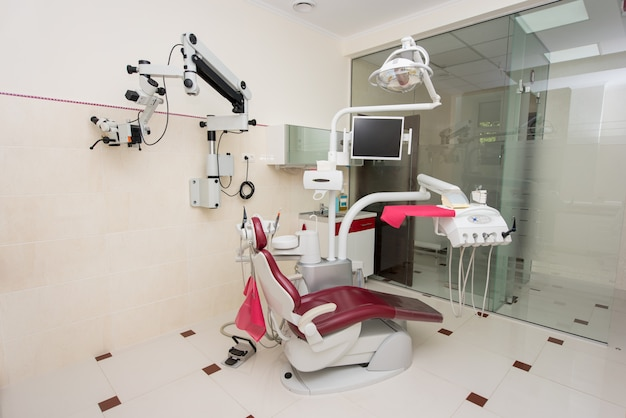Unidade dentária moderna com ferramentas de alimentação superior, cadeira vermelha, microscópio, tela, equipamentos e acessórios