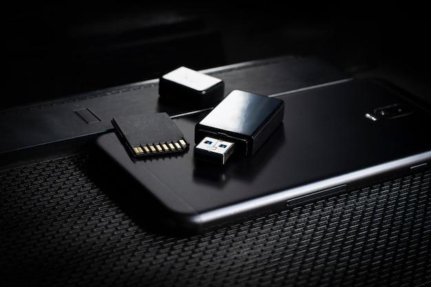 Unidade flash usb e smartphone acima do computador. coloque na mesa de escritório / foco seletivo
