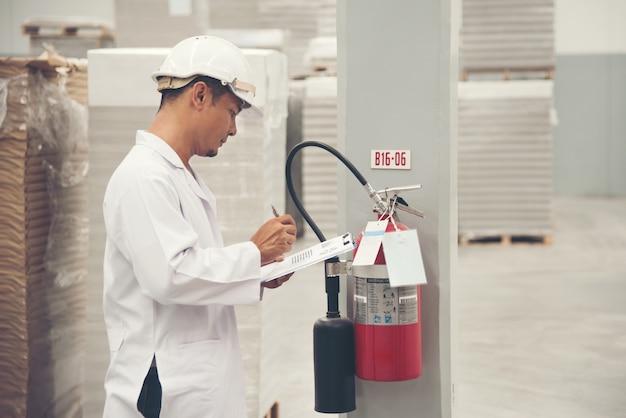 Uniforme branco do homem novo que verifica o equipamento de segurança na fábrica tailândia da loja.