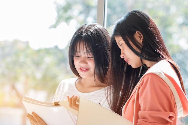 Universidade asiática ou estudantes universitários estudando juntos com papel de tablet e documentos