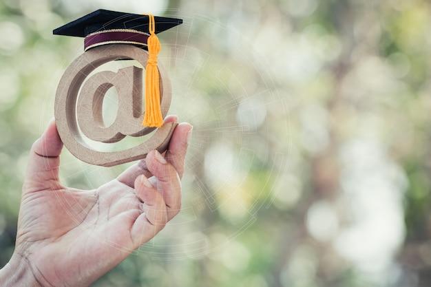 Universidade de aprendizagem online no conceito de educação no exterior: chapéu de formatura no símbolo de endereço de e-mail na mão do aluno. escola internacional de comunicação de ideias pode aprender curso de tecnologia da internet