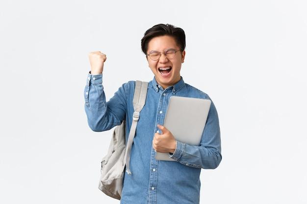 Universidade, estudo no exterior e conceito de estilo de vida. feliz regozijando o estudante masculino asiático com aparelho triunfante, passar nos exames, terminar o semestre final, levantar o punho e gritar sim com satisfação, segurar o laptop.