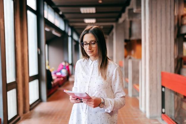 Universitária bonita com cabelos castanhos e óculos em pé no corredor e segurando um caderno.