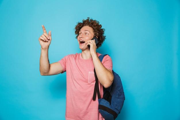 Universitário, com cabelos cacheados, vestindo roupas casuais e mochila, olhando de lado enquanto fala no smartphone
