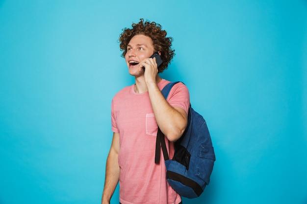 Universitário, com cabelos cacheados, vestindo roupas casuais e mochila, sorrindo e falando no smartphone