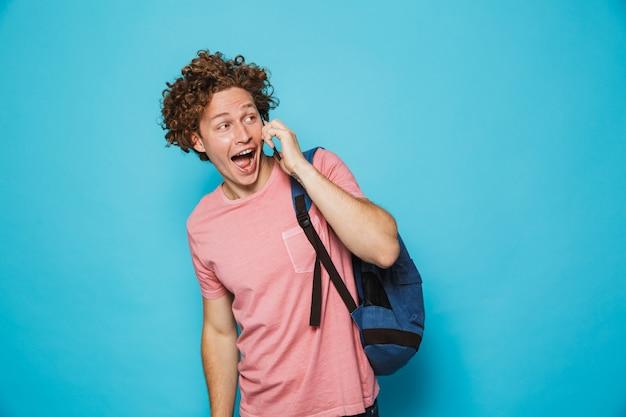 Universitário feliz com cabelos cacheados, vestindo roupas casuais e mochila, olhando de lado enquanto fala no smartphone