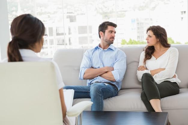 Unmmiling couple conversando com seu terapeuta