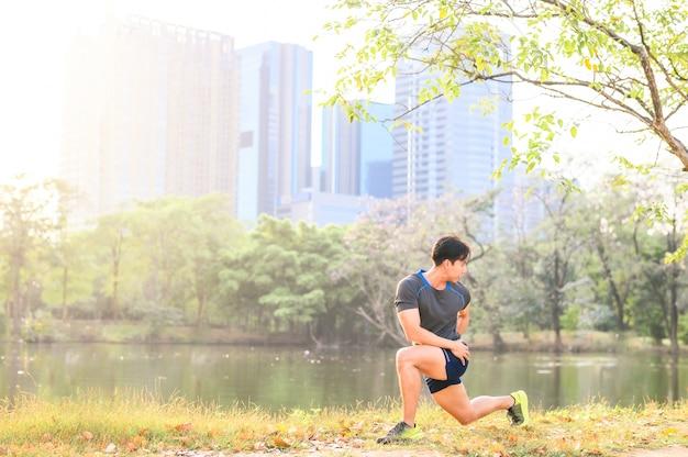 Unner fazendo exercícios de alongamento, aqueça na luz do sol da manhã na mochila