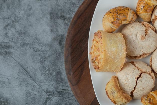 Unte os biscoitos com o açúcar em pó em um prato de cerâmica branca.