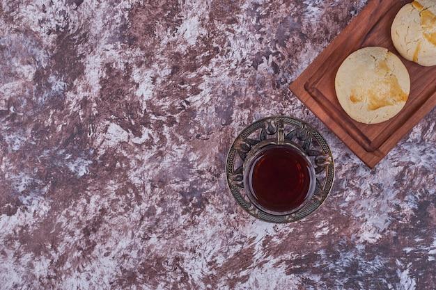 Unte os cookies com manteiga em uma travessa de madeira com um copo de chá. foto de alta qualidade