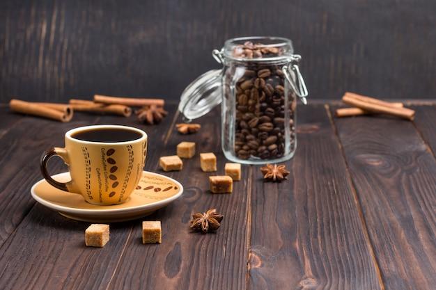 Ð¡up de café, grãos de café em potes de vidro. na mesa, paus de canela