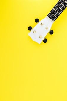 Uquelele branca sobre um fundo amarelo e com um lugar para texto. conceito musical. configuração plana