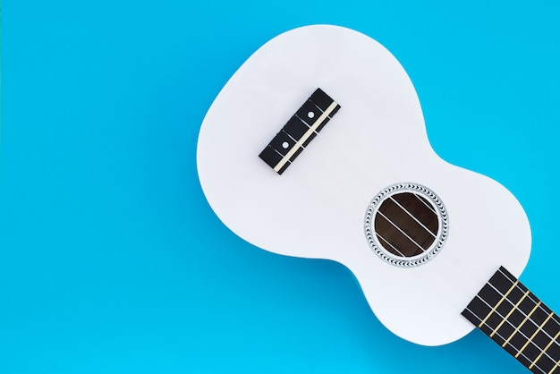 Uquelele branco sobre um fundo azul. conceito musical. flat lay ukulel. lugar para texto