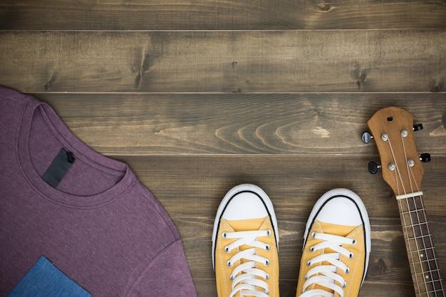 Uquelele, camisa e sapatos no antigo fundo de madeira com espaço de cópia. lay plana