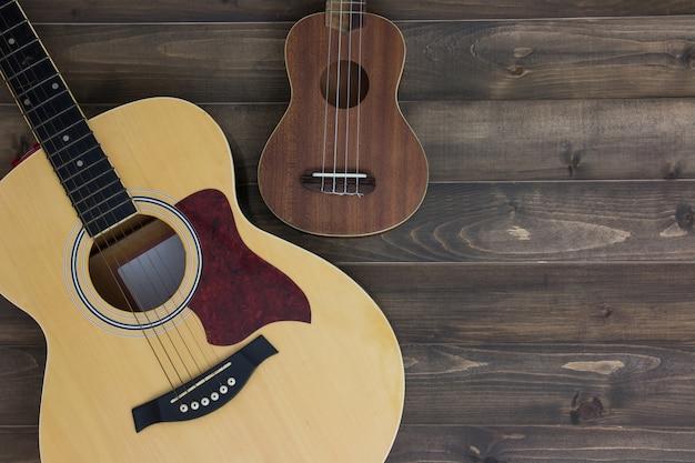 Uquelele da guitarra dos instrumentos musicais no fundo de madeira velho com espaço da cópia. efeito vintage.