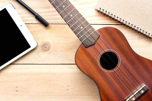 Uquelele do close-up, tablet pc e caderno no fundo de madeira. sobre a luz
