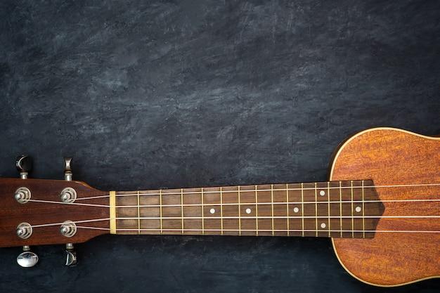 Uquelele no fundo preto do cimento. pescoço e cordas de peças de ukulele. copyspace conceito de instrumentos musicais havaianos e melómanos.