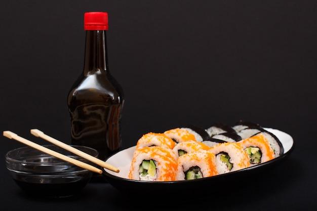 Uramaki california. rolinhos de sushi com nori, arroz, pedaços de abacate, pepino, decorado com ovas de peixe voador no prato de cerâmica. garrafa e tigela com molho de soja. culinária japonesa. profundidade superficial de campo