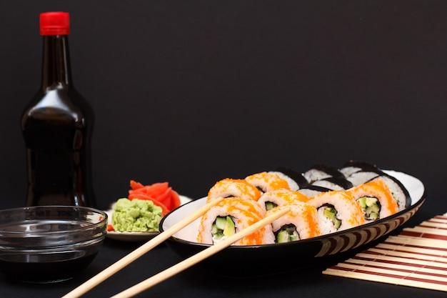 Uramaki california. rolinhos de sushi com nori, arroz, pedaços de abacate, pepino, decorado com ovas de peixe voador no prato de cerâmica. garrafa e tigela com molho de soja. prato com gengibre em conserva vermelho e wasabi.