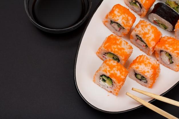 Uramaki california. rolinhos de sushi com nori, arroz, pedaços de abacate, pepino, decorado com ovas de peixe voador no prato de cerâmica. tigela com molho de soja. culinária japonesa. vista do topo.