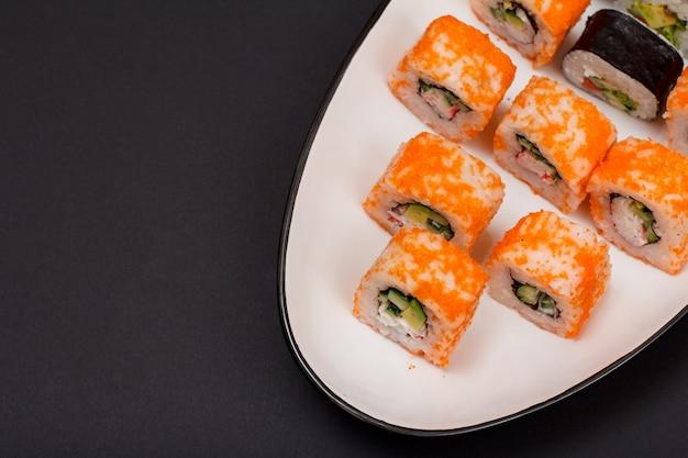 Uramaki california. rolinhos de sushi com nori, arroz, pedaços de abacate, pepino, decorado com ovas de peixe voador no prato de cerâmica. vista do topo. fundo preto.