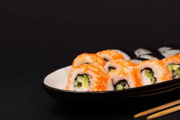 Uramaki california. rolinhos de sushi com nori, arroz, pedaços de abacate, pepino, decorado com ovas de peixe voador num prato de cerâmica com palitos de madeira. fundo preto.