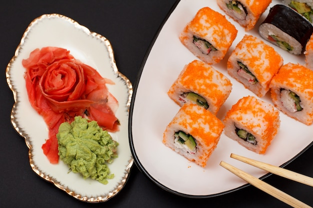 Uramaki california. rolinhos de sushi com nori, arroz, pedaços de abacate, pepino, decorado com ovas de peixe voador num prato de cerâmica com palitos de madeira. prato com gengibre em conserva vermelho e wasabi. vista do topo.