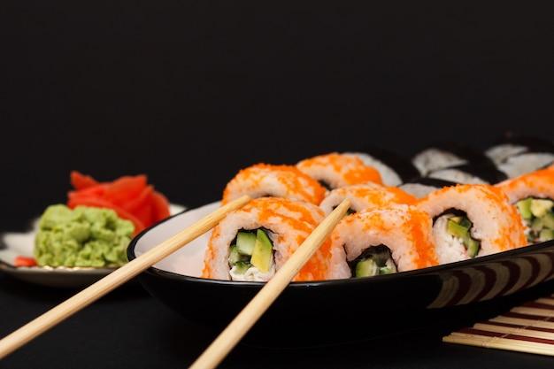 Uramaki california. rolinhos de sushi com nori, arroz, pedaços de abacate, pepino, decorado com ovas de peixe voador num prato de cerâmica com palitos de madeira. prato com gengibre em conserva vermelho e wasabi.