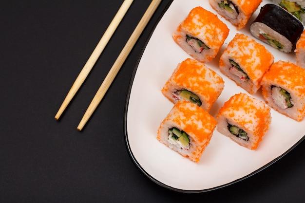 Uramaki california. rolinhos de sushi com nori, arroz, pedaços de abacate, pepino, decorado com ovas de peixe voador num prato de cerâmica com palitos de madeira. vista do topo.