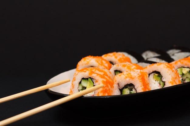 Uramaki california. rolinhos de sushi com nori, arroz, pedaços de abacate, pepino, decorado com ovas de peixe voador num prato de cerâmica com palitos de madeira.