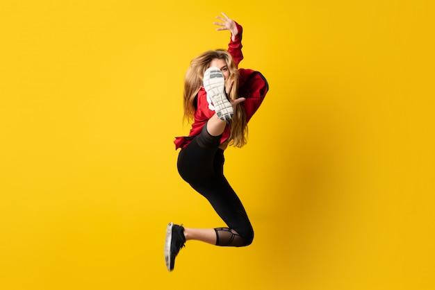 Urban ballerina dançando sobre amarelo isolado e pulando