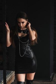 Urbana garota elegante vestido de couro sexual perto de grade de metal.