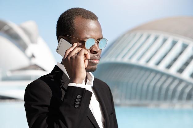 Urbano jovem bonito profissional morena usando aparelho eletrônico ao ar livre. na moda, procurando empresário preto fazendo negócios, falando no celular com seu parceiro, tendo um olhar sério