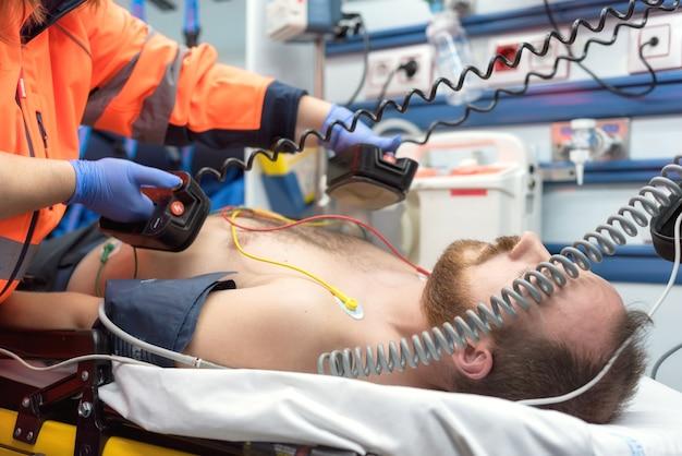 Urgência médica na ambulância. médico de emergência usando desfibrilador